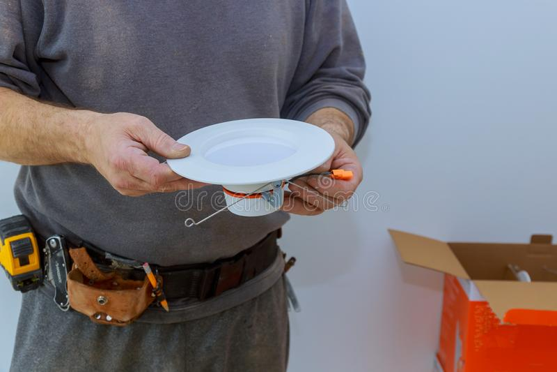 Os eletricistas de poupança de energia estão substituindo como a luz de poupança de energia do diodo emissor de luz da instalação imagens de stock