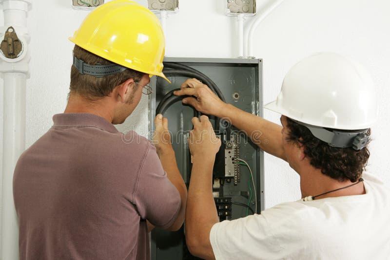 Os eletricistas instalam o painel imagens de stock royalty free