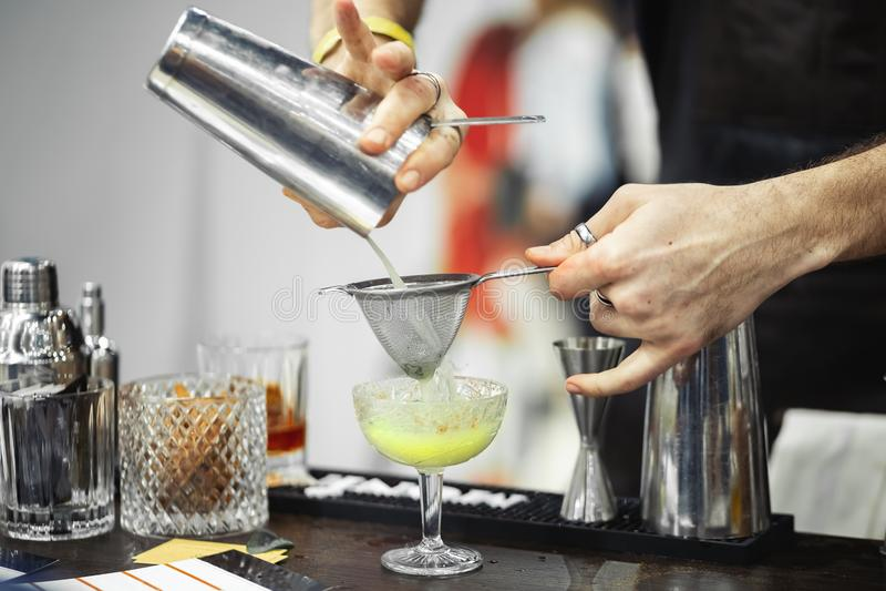 Os empregado de bar fazem o cocktail foto de stock