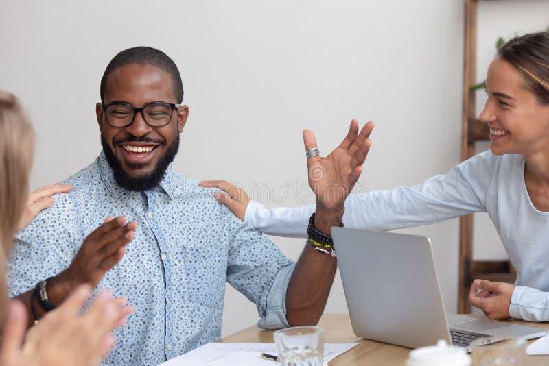 Os empregados caucasianos amigáveis da equipe batem o colega africano no ombro fotos de stock