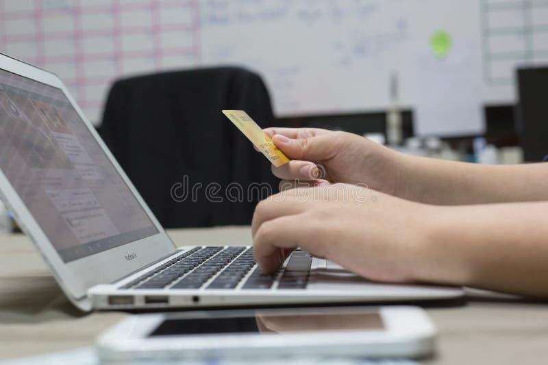 Os empregados da empresa estão comprando produtos em linha e estão pagando-os através dos cartões de crédito em linha conveniente fotografia de stock