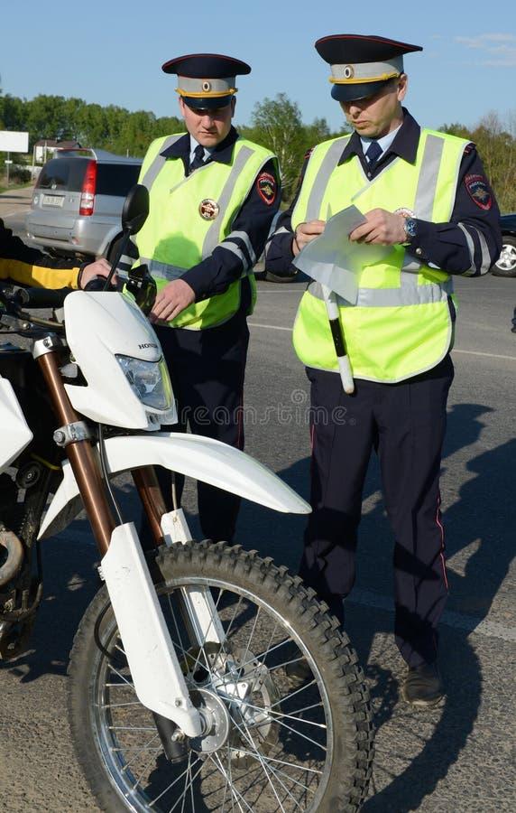 Os empregados da polícia de trânsito inspecionam o velomotor na trilha fotos de stock royalty free