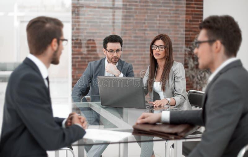 Os empregados do banco trabalham com os clientes na mesa imagem de stock
