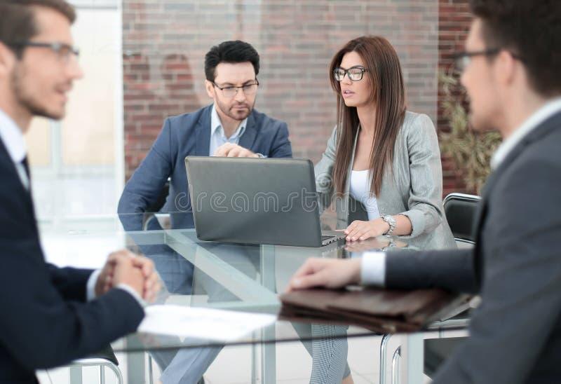 Os empregados do banco trabalham com os clientes na mesa foto de stock
