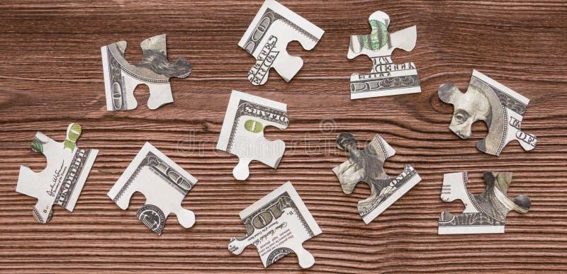 Os enigmas do dinheiro de cem-dólar das cédulas são desmontados na perspectiva de uma textura de madeira natural fotos de stock royalty free