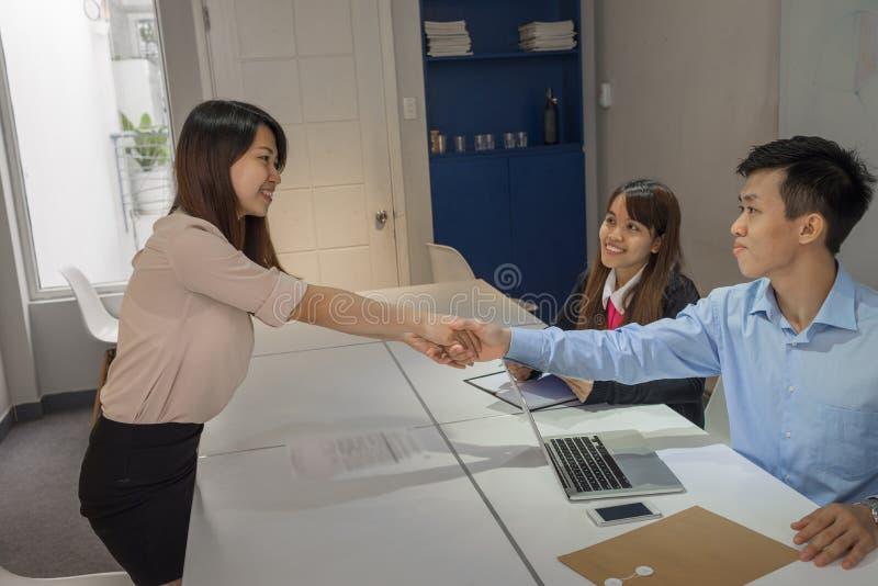 Os entrevistador felicitam o candidato novo em passar a entrevista foto de stock