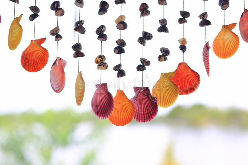 Os escudos móveis que penduram pela corda para decoram na janela da casa foto de stock