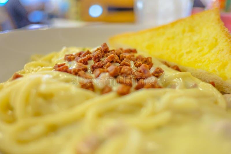 Os espaguetes ascendentes próximos do carbonara enchem com pão secado do bacon e da manteiga foto de stock