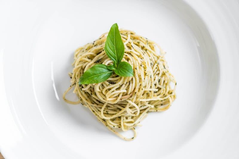 os espaguetes da massa com pesto esverdeiam o molho e a manjericão foto de stock