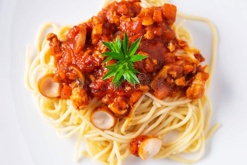 Os espaguetes deliciosos serviram em uma placa branca na tabela de madeira imagem de stock