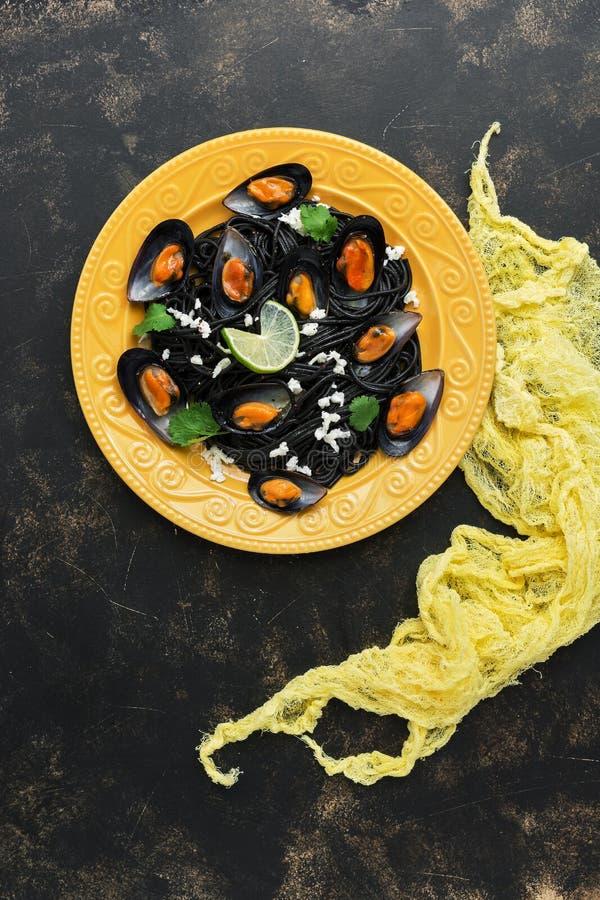 Os espaguetes pretos da massa com mexilhões serviram em uma placa amarela, fundo arborizado Vista superior, espaço da cópia imagem de stock