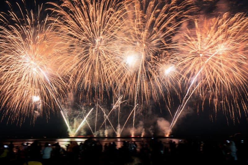 Os espectadores estão olhando fogos de artifício coloridos no céu noturno na praia fotografia de stock
