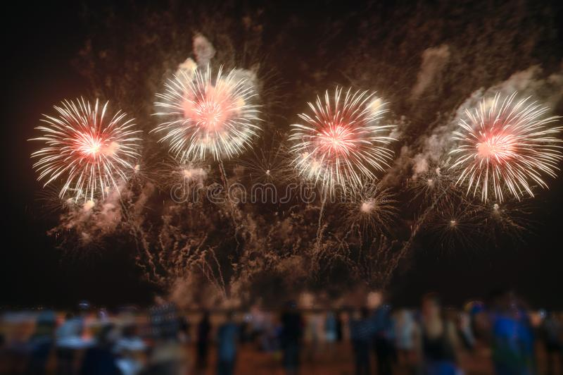 Os espectadores estão olhando fogos de artifício coloridos no céu noturno na praia imagens de stock