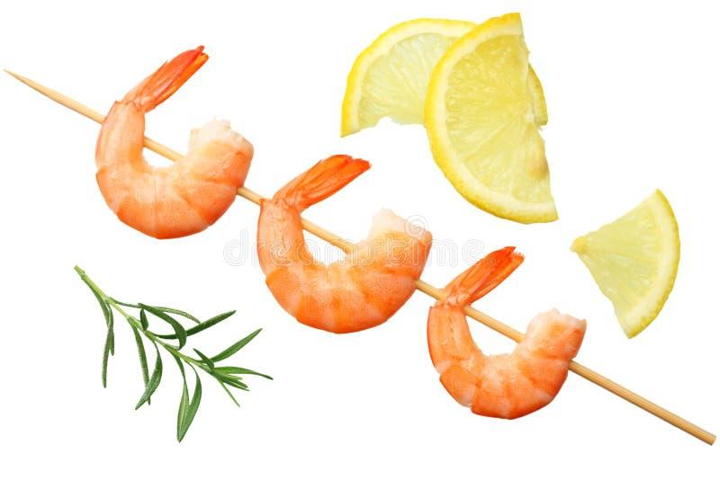 os espetos dos camarões com limão e alecrins isolaram-se em um fundo branco Vista superior imagens de stock royalty free