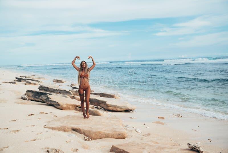Os esportes delgados novos modelam restos na praia e apreciam o vento morno do mar A menina está puxando suas mãos para fotos de stock