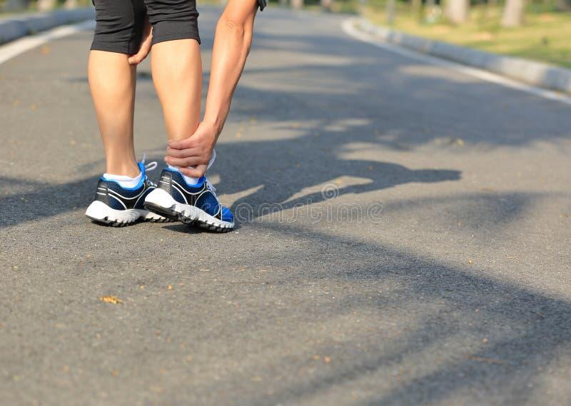 Os esportes do corredor da mulher feriram o joelho imagem de stock royalty free