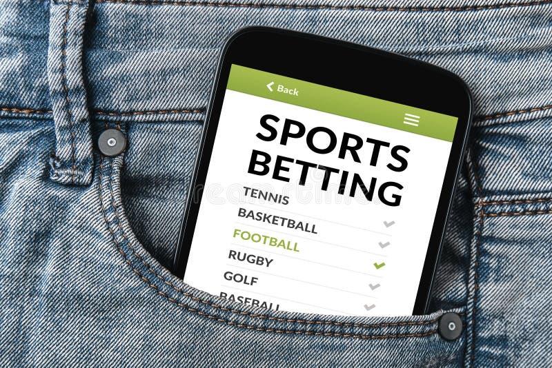 Os esportes que apostam o conceito na tela do smartphone nas calças de brim pocket foto de stock