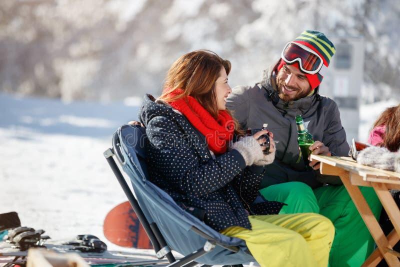 Os esquiadores acoplam beber e falar no café no esqui foto de stock royalty free