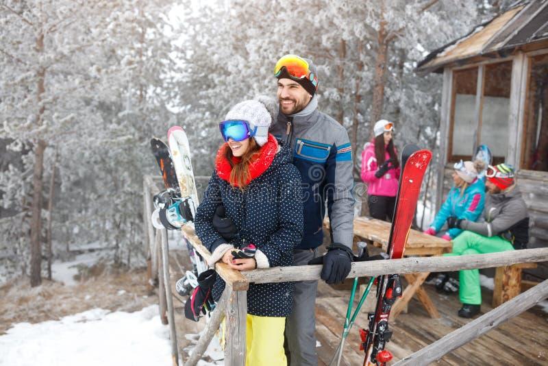 Os esquiadores acoplam-se na casa de madeira do inverno fotografia de stock