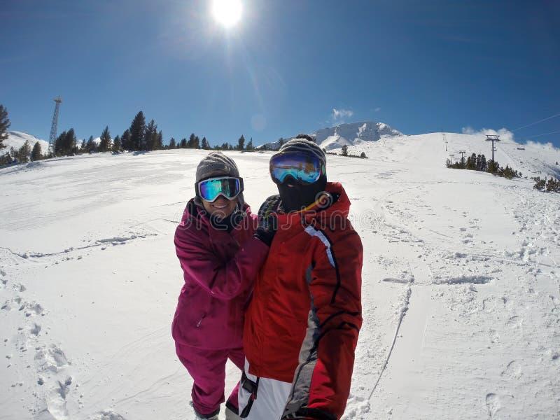 Os esquiadores acoplam-se no terreno branco do esqui imagens de stock