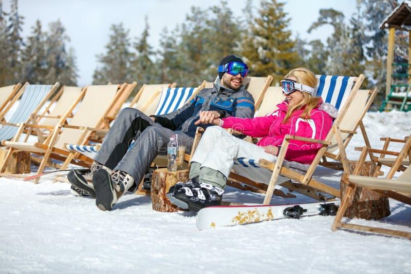 Os esquiadores acoplam-se no vadio do sol apreciam no sol fotos de stock royalty free