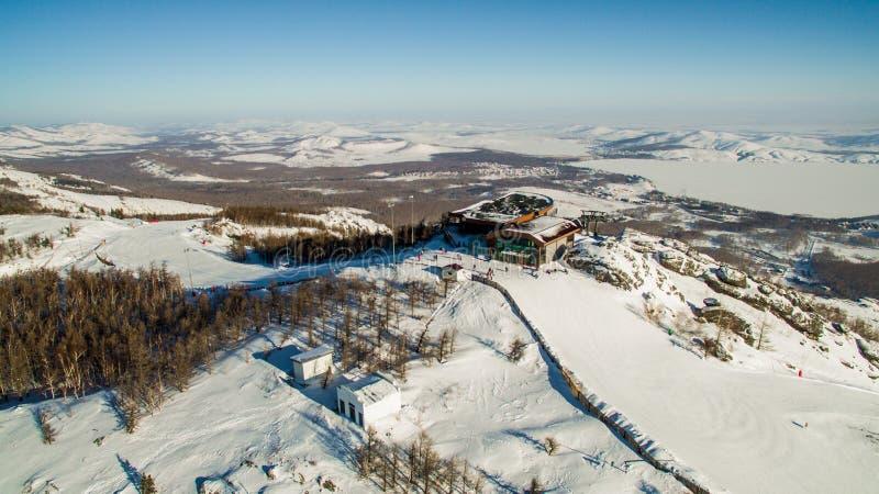 Os esquiadores e os snowboarders deslizam para baixo a montanha perto do lago Bannoe aéreo foto de stock