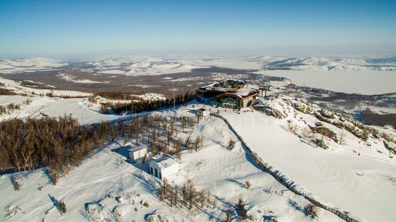 Os esquiadores e os snowboarders deslizam para baixo a montanha perto do lago Bannoe aéreo fotos de stock