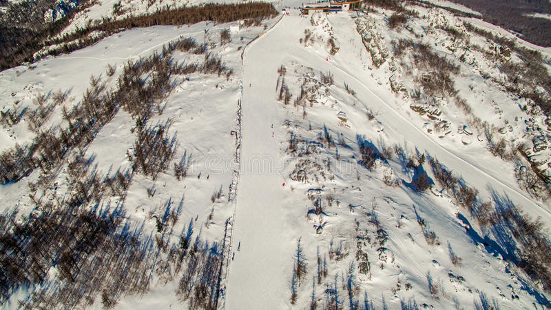 Os esquiadores e os snowboarders deslizam para baixo a montanha perto do lago Bannoe aéreo fotos de stock royalty free