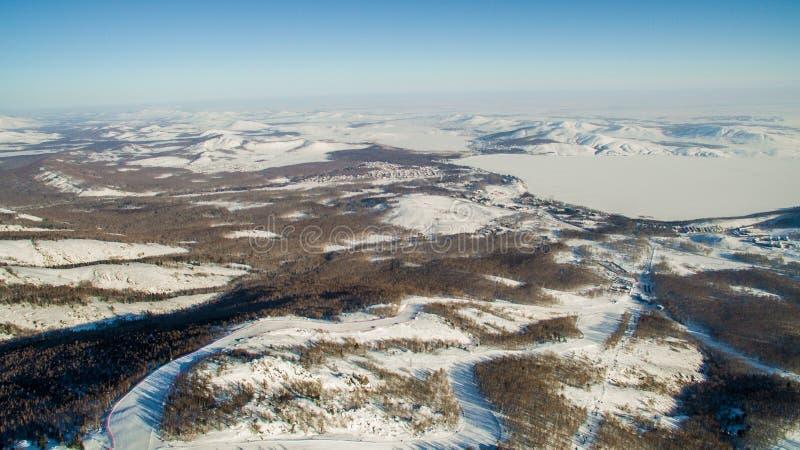 Os esquiadores e os snowboarders deslizam para baixo a montanha perto do lago Bannoe aéreo imagens de stock