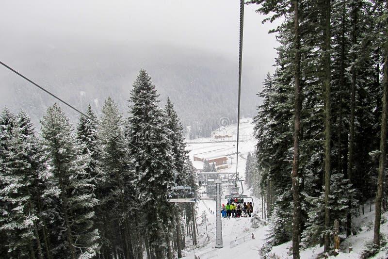 Os esquiadores e os snowboarders escalam acima a inclinação em um elevador de cadeira do six-seater na floresta coberto de neve imagens de stock royalty free