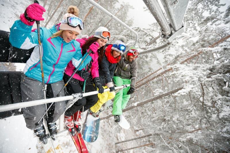Os esquiadores felizes dos amigos no elevador de esqui montam acima na inclinação do esqui em d nevado fotos de stock royalty free