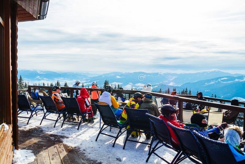 Os esquiadores sentam-se em cadeiras perto de um restaurante sobre uma montanha Povos no resto e na bebida dos ternos de esqui imagens de stock royalty free
