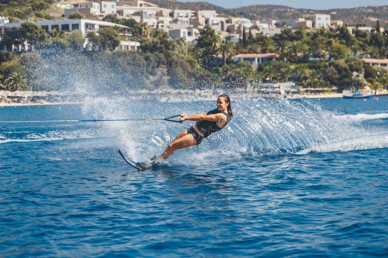 Os esquis de água deslizam nas ondas, atleta fêmea no Mar Egeu, Grécia foto de stock royalty free