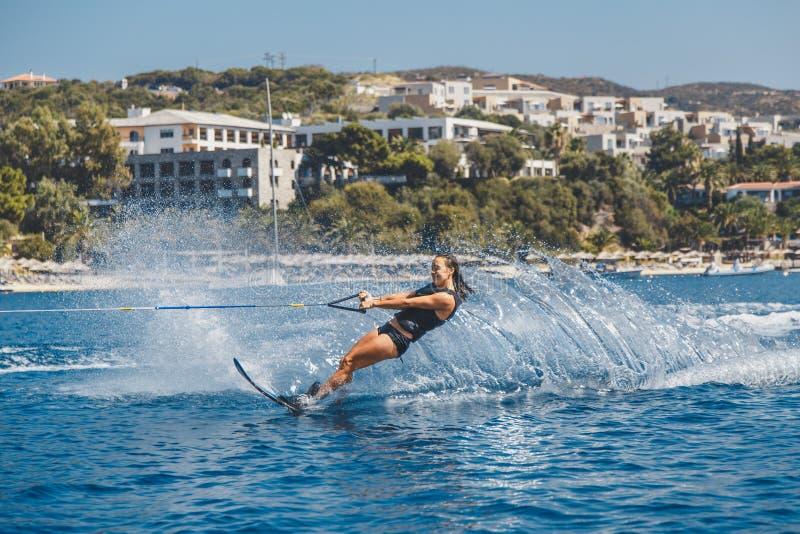 Os esquis de água deslizam nas ondas, atleta fêmea no Mar Egeu, Grécia imagens de stock