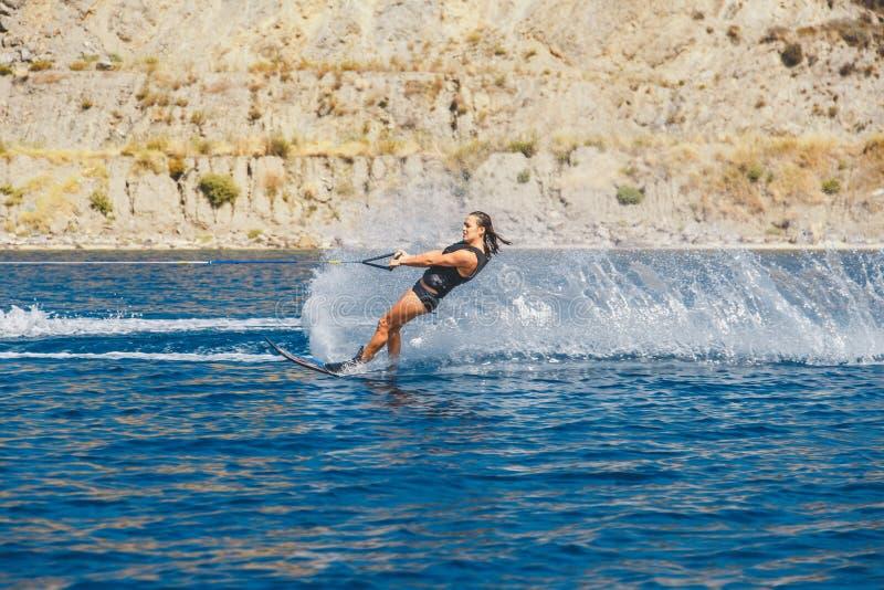 Os esquis de água deslizam nas ondas, atleta fêmea no Mar Egeu, Grécia imagens de stock royalty free