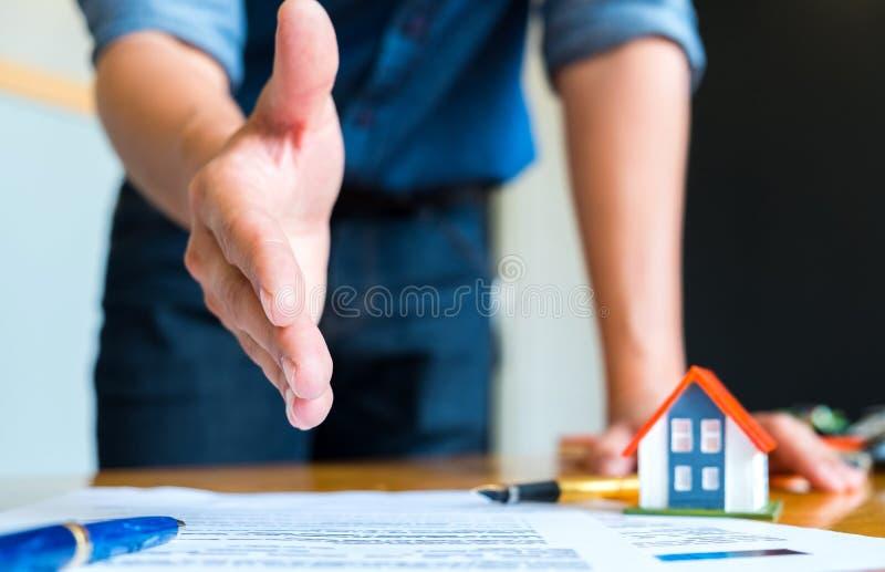 Os estiramentos home do vendedor a agitam as mãos, a casa da pena e do modelo em h imagem de stock
