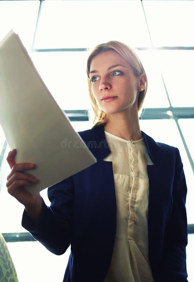os estudantes à moda novos que leem com cuidado o texto foto de stock royalty free