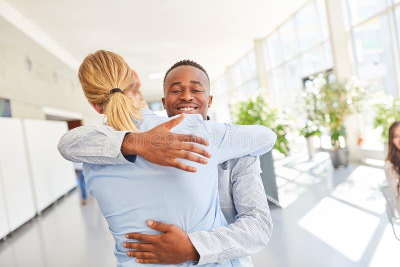 Os estudantes abraçam-se após a conclusão do diploma imagem de stock royalty free