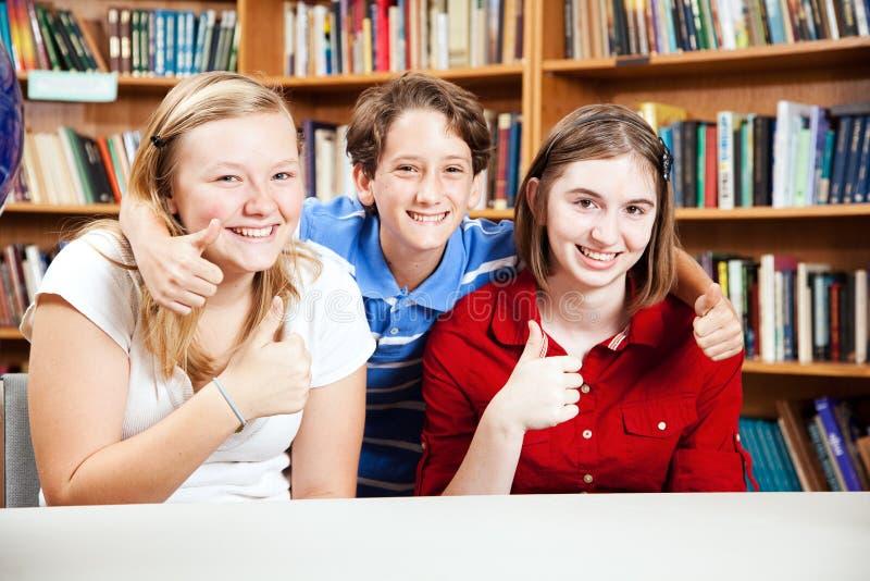 Os estudantes da biblioteca dão os polegares acima imagens de stock royalty free