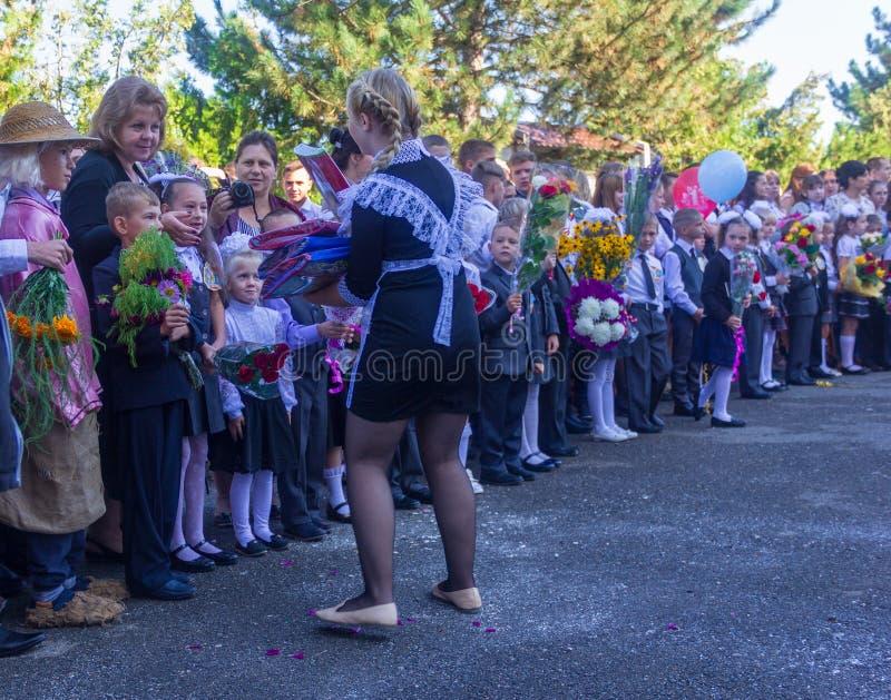 Os estudantes da High School dão presentes aos primeiro-graduadores feriado conhecimento dia o 1º de setembro fotografia de stock