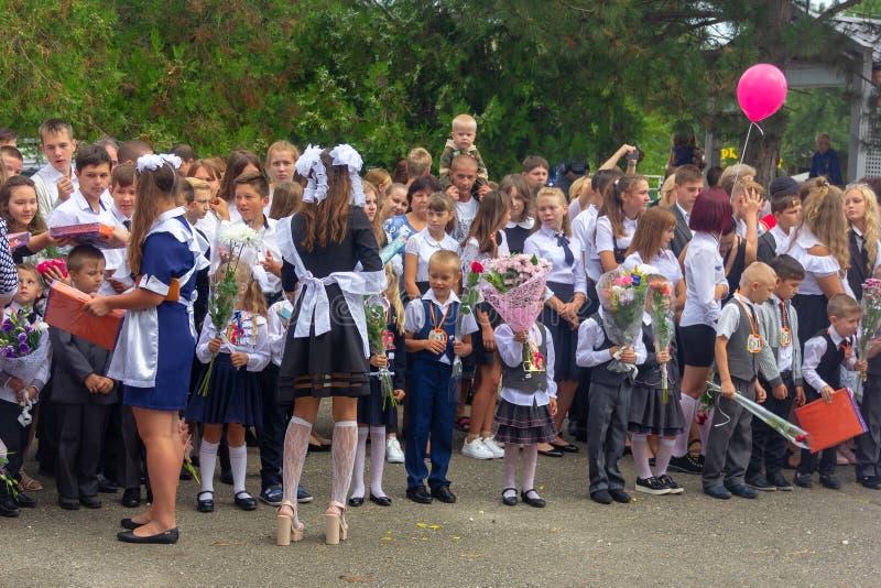 Os estudantes da High School das meninas d?o presentes aos primeiro-graduadores na parada no dia do conhecimento fotos de stock royalty free