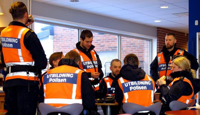 Os estudantes da polícia falam e bebem o café fotos de stock
