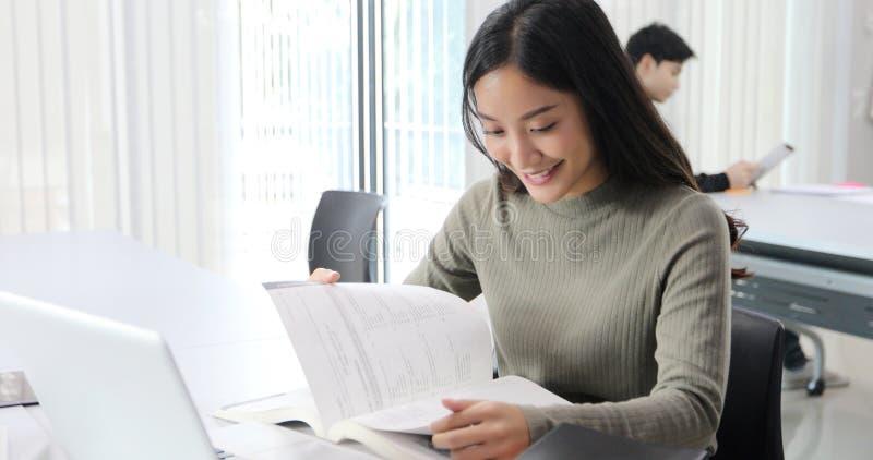 Os estudantes de mulheres asiáticos sorriem e o livro de leitura e caderno da utilização para que as ajudas compartilhem de ideia foto de stock royalty free