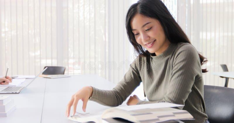 Os estudantes de mulheres asiáticos sorriem e o livro de leitura e caderno da utilização para que as ajudas compartilhem de ideia imagem de stock royalty free