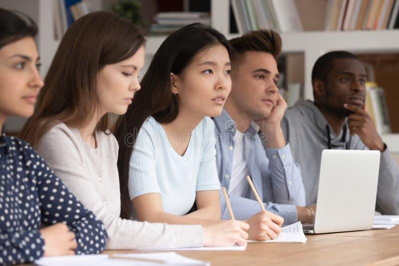 Os estudantes diversos concentrados escutam a leitura do professor imagem de stock