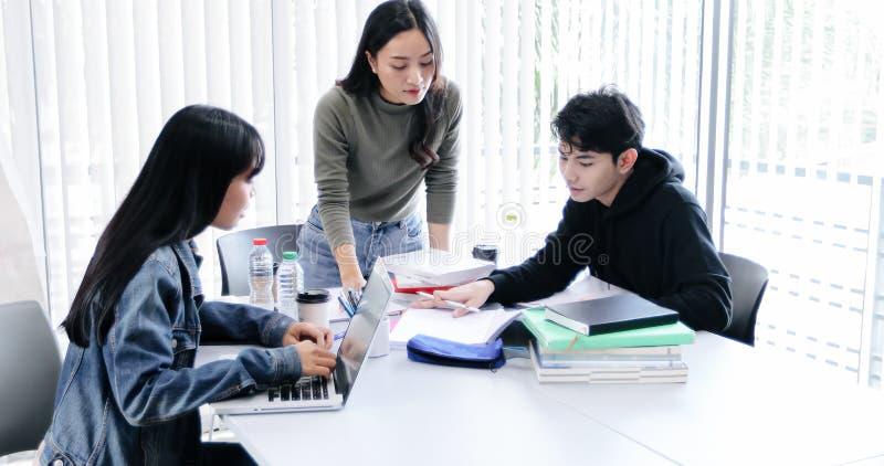 Os estudantes do grupo sorriem e t?m o divertimento e tabuleta que da utiliza??o igualmente ajuda a compartilhar de ideias no tra foto de stock