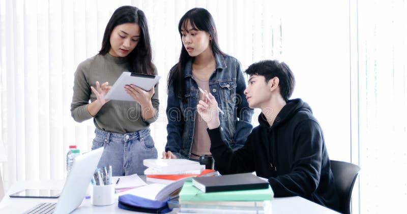 Os estudantes do grupo sorriem e t?m o divertimento e tabuleta que da utiliza??o igualmente ajuda a compartilhar de ideias no tra fotos de stock