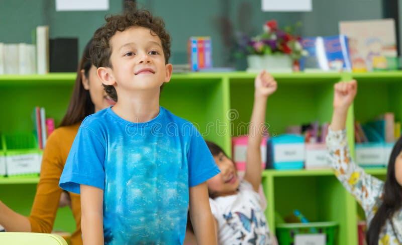 Os estudantes do jardim de infância levantam-se na sala de aula, internatio pré-escolar foto de stock