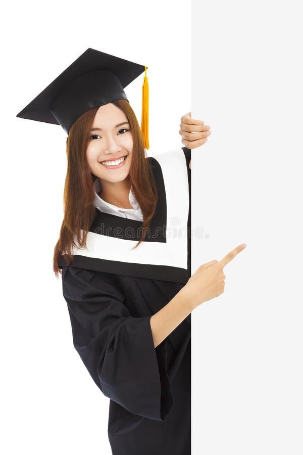 Os estudantes fêmeas novos da graduação apontam à placa vazia fotografia de stock royalty free