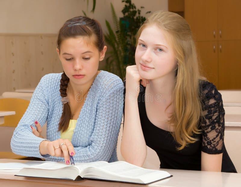 Os estudantes fêmeas são acoplados na sala de aula fotos de stock